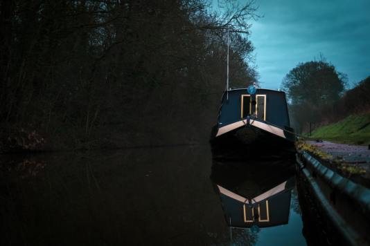 There's no brick wall and triple bolted door, off-grid on a narrowboat, at night.